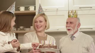 Family Celebrating The Grandfather's Birthday. Elderly Man Blows Out Candles On The Cake.