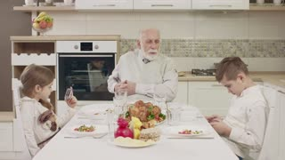 Grandpa Communicates With Grandchildren At The Table Before A Family Dinner. Family Toasting At Dinner Table At Home In Kitchen