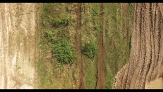 Military tank in movement on a dirt ground terrain. Aerial View