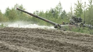 Military tank in movement on a dirt ground terrain.