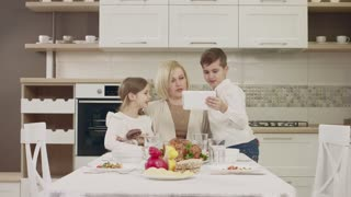 Mom Communicates With Her Children At The Table During A Family Dinner. Family Toasting At Dinner Table At Home In Kitchen