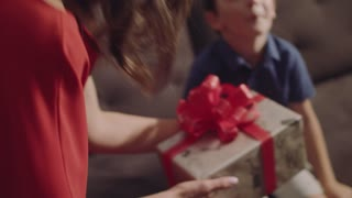 The Family Is Celebrating The Birthday Of His Son. Boy With Mother Open A Birthday Gift.