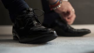 The man wears shoes. Tie the laces on the shoes. Men's style. Groom Tied The Laces On The Shoes.