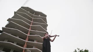 Woman In Evening Dress Playing The Violin On. Beautiful Young Woman Near The Building.