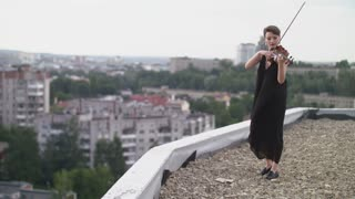 Woman In Evening Dress Playing The Violin On. Beautiful Young Woman On The Roof Of The Building.