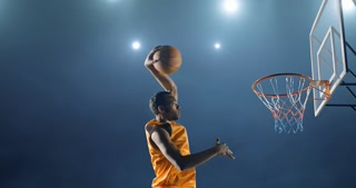 4k footage - close up image of professional basketball player making slam dunk during basketball game in floodlight basketball court. The player is wearing unbranded sport clothes.