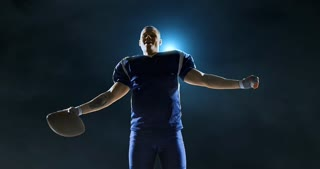 American football player is cheering on dark background