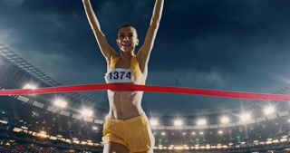 Track and field female  runner crosses finishing line