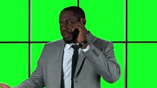Afro-american businessman with cellphone. Man on chromakey background smiling.