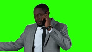 Afro-american businessman with phone. Smiling man on green background.