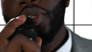 Afro-american man singing isolated. Closeup of guy holding microphone. Single from debut album.