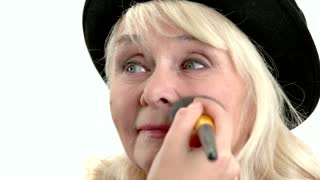 Applying makeup on elderly lady. Female hand holding cosmetic brush.
