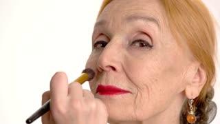 Applying makeup on senior woman. Hand of visagist with brush. Best beauty tips.
