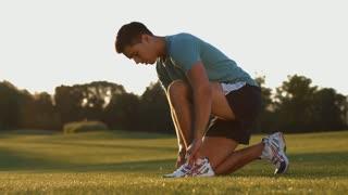 Athlete preparing for cross-country. Morning running. Guy tying shoelaces on sneakers. Sporsmen preparing to run.