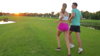 Athletes run on sunset background. Guy and girl running on the golf field. Warm up in the fresh air. Sports on the nature.