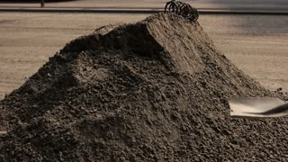 Big pile of dirt. Worker with a shovel. Renewal of town roads. Work double shifts.