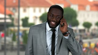 Black businessman with phone smiling. Happy guy on street background. Flirting tips for guys.