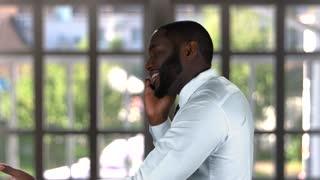 Black male talking on phone. Businessman on window background.
