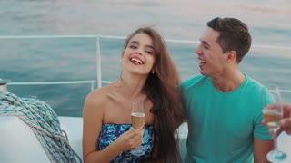 Boy and girl drink champagne on the yacht and having fun. Guy flirting with a girl. Cheerful young people relaxing on the boat. Friendly company walk on the yacht. Guy and girl laughing.