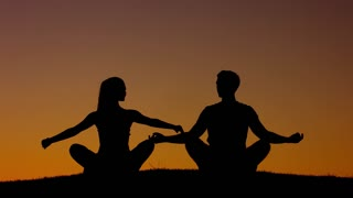 Boy and girl engage in yoga on the nature. A man and a woman meditating in the mountains. People relax at sunset.