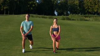 Boy and girl go in for sport on the street. Fitness outdoors. Two trainers show sports exercise on green meadow.