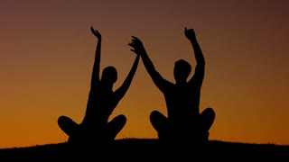 Boy and girl waving their hands at sunset. Silhouette figures of people at sunset. People relax. Rest at nature.