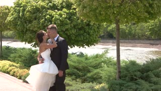 Bride and groom kissing outdoors. Wedding couple near water. Happiness and marriage. The new life awaits.