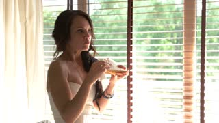 Bride eating a sandwich. Young woman near a window. Hungry and nervous. Bread and cheese.