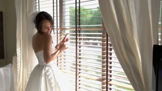 Bride standing near window. Woman touching her dress. Look like a queen. Few minutes before wedding ceremony.