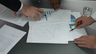 Business documents and hands. Papers with charts on table. Teamwork is essential.
