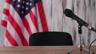Businessman sitting beside american flag. Man speaks into microphone. People need answers. Honesty is always valued.
