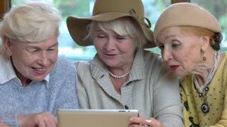 Cheerful senior women with tablet. Ladies talking and laughing.