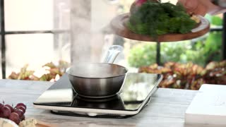 Chef adding ingredient. Walnuts and boiling liquid. Roquefort sauce recipe.