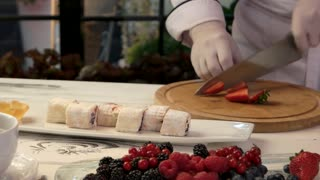 Chef cutting strawberry. Plate with fruit sushi rolls. How to prepare sweet delicacy.