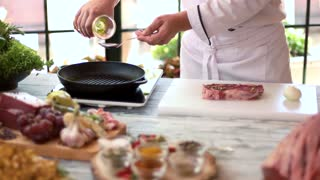 Chef pouring oil on pan. Raw beef steak and onion. Useful kitchen tips.