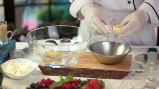 Chef separating egg yolk. Bowls with food ingredients.