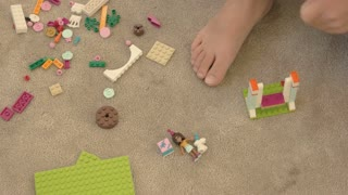Child playing with plastic constructor. Toys on carpet background. Think and create.