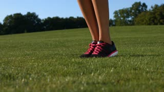 Close-up of jumping feet on the jump rope. Outdoor sports. Girl jumping on a skipping rope on a green grass.