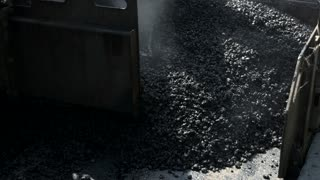 Construction machine laying asphalt. Movement of road paver. Hot tar mixed with stones. Use only best construction materials.