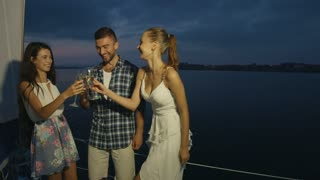 Corporate rest. Guy and girl drinking champagne on the yacht. Party on the yacht. Night walk along the river on a yacht.