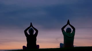 Couple does yoga. People sitting on sunset background. Eternal search of harmony. Mind and body.