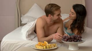 Couple eating in bed. Plates with fruit in bedroom. Share with me. Romantic breakfast for two.