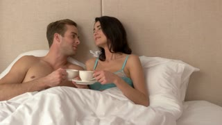 Couple holding cups in bed. Man smiling and kissing woman. You are my joy. Romance raises mood.