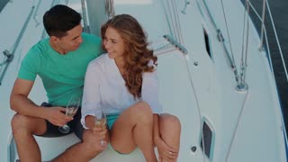 Couple in love drinking champagne on the yacht. Young people laugh. Sea voyage on the yacht. Love story.