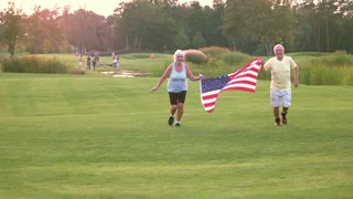 Couple with American flag. Front view of running people. Veterans of the sport. Victories and patriotism.