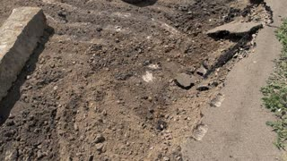 Damage of road surface. Concrete pieces on the ground. Dust and dirt. City roads need capital repair.