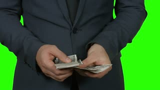 Dollars counting on green background. Man putting money into pocket. Build a stable income.