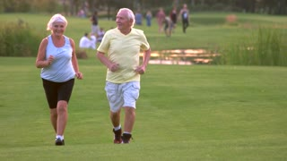 Elderly couple jogging. People smiling and running. Former professional athletes. Health of cardiovascular system.