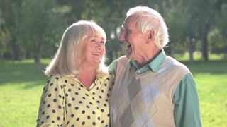 Elderly couple laughing. Man with woman outdoor. I love your jokes. Great mood every day.