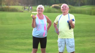 Elderly couple with dumbbells. People doing exercise and smiling. Sportsmen never get old. Mood and motivation.